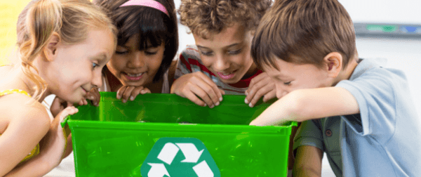 Several children looking in a recycling bin